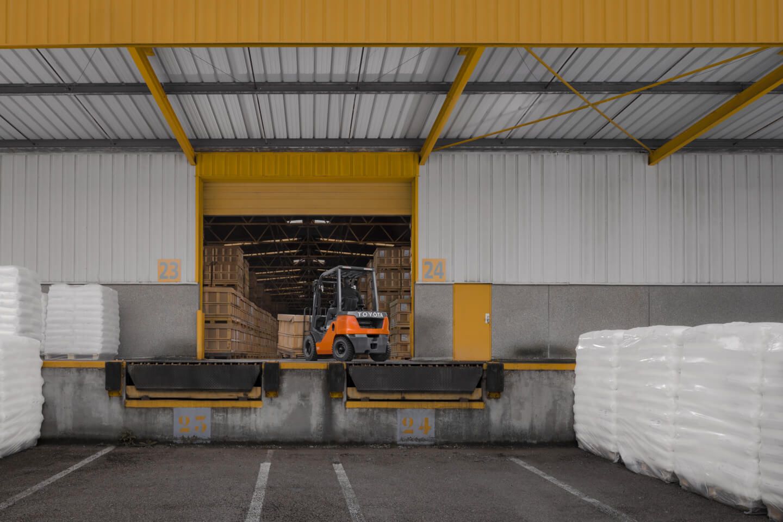 carretilla contrapesada en un muelle de carga entrando mercancía al almacén