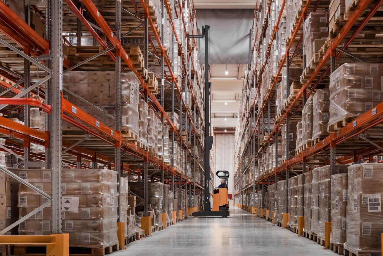carretilla retráctil en el interior de un almacén colocando un pallet en altura