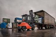 carretilla contrapesada cargando un camión en el exterior