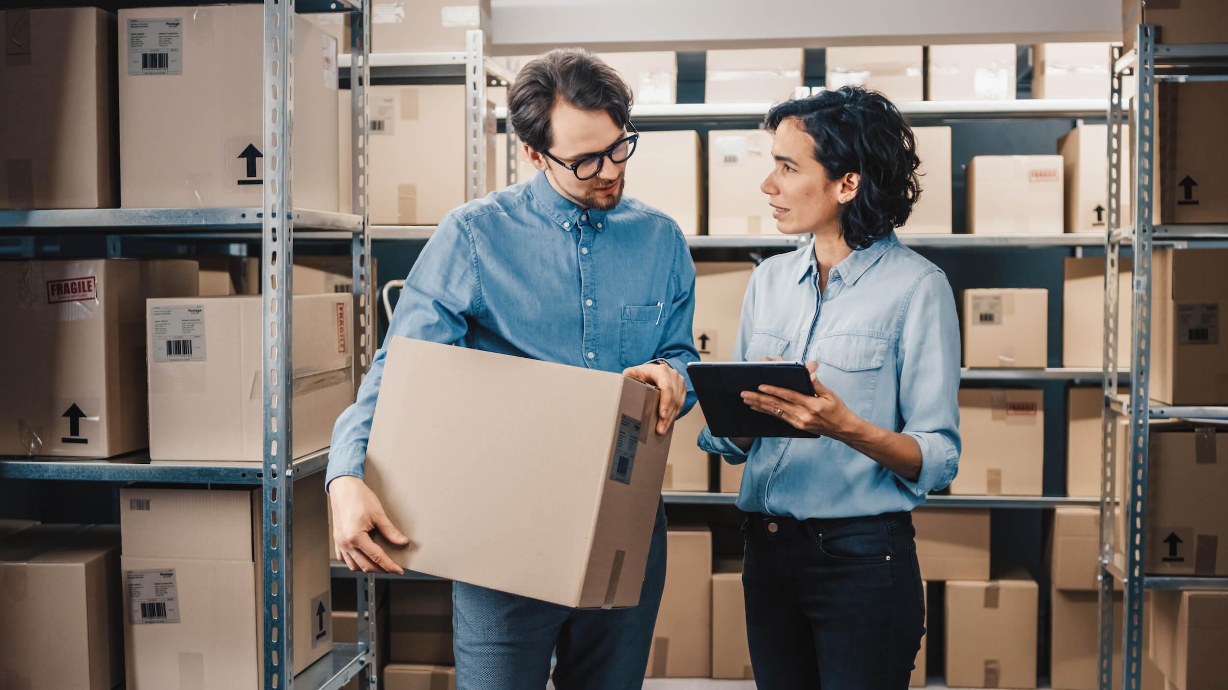 dos personas en el almacén preparando un pedido