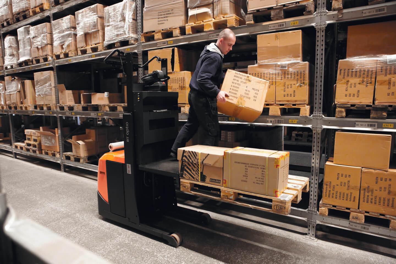 operario colocando caja en un preparador de pedidos